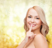 Beautiful young woman pointing finger to lips — Foto Stock