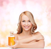 Happy woman with oil bottle — Stockfoto