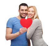 Smiling couple holding big red heart — ストック写真