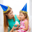Mother and daughter in blue hats with cake — Stock Photo