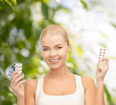 Smiling young woman with pills — Stock Photo