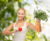 Smiling woman holding heart symbol and carrots — ストック写真