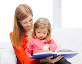 Happy mother and daughter with book — Stock Photo