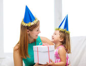 Mother and daughter in blue hats with favor horns — Stock Photo