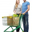 Smiling couple with shopping cart and food in it — Stock Photo #41706793