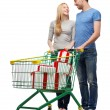 Smiling couple with shopping cart and gift boxes — Stock Photo #41706937