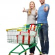 Smiling couple with shopping cart and gift boxes — Stock Photo #41706969