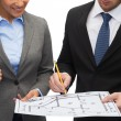 Businesspeople with clipboard, blueprint, helmet — Stock Photo