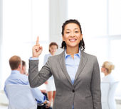 Smiling businesswoman with her finger up at office — Stock Photo