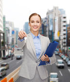 Smiling businesswoman with folder and keys — Stock Photo