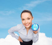 Smiling businesswoman with blue clock — Стоковое фото