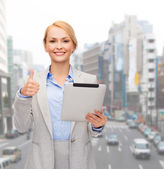 Smiling woman with tablet pc showing thumbs up — Stock Photo