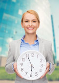 Smiling businesswoman with wall clock — Stock fotografie
