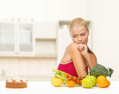 Doubting woman with fruits and pie — Stock Photo