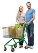 Smiling couple with shopping cart and food in it — Stock Photo