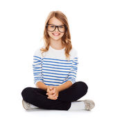 Smiling girl in eyeglasses sitting on floor — Zdjęcie stockowe