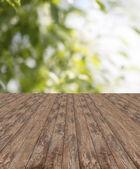 Wooden floor and green plants — Stock Photo