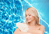 Smiling woman with exfoliation glove — Stockfoto