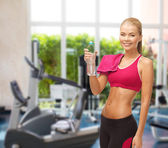 Smiling woman with bottle of water at gym — ストック写真