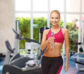 Smiling woman with bottle of water at gym — Stok fotoğraf