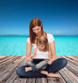 Happy mother with little girl and tablet pc — Stock fotografie