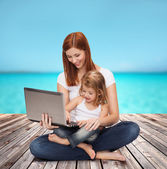 Happy mother with adorable little girl and laptop — Zdjęcie stockowe