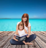 Happy mother with adorable little girl and book — Stock Photo