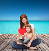 Happy mother with adorable little girl and heart — Stok fotoğraf