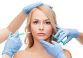 Woman face and beautician hands with syringes — Foto de Stock