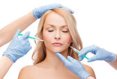 Woman face and beautician hands with syringes — Stok fotoğraf
