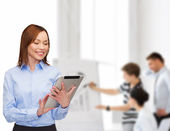 Smiling woman looking at tablet pc at office — Stock Photo