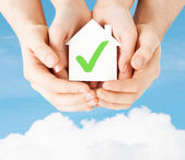 Hands holding house with check mark — Stock Photo