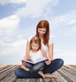 Happy mother with adorable little girl and book — Stok fotoğraf