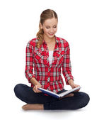 Smiling young woman sittin on floor with book — Stock Photo