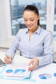 Businesswoman with laptop and charts in office — Stock Photo