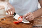 мужской ручной резки помидор на борту с ножом — Стоковое фото