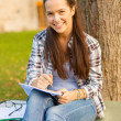 Smiling teenager writing in notebook — Stock Photo #41960841