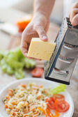 Close up of male hands grating cheese over pasta — Stock Photo