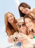 Sonrientes chicas tomando fotos en café en la playa — Foto de Stock