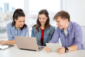 Three smiling students with laptop and tablet pc — Stok fotoğraf