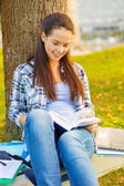Smiling teenager reading book — Stock Photo