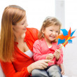 Stock Photo: happy mother and daughter with pinwheel toy