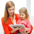 Stock Photo: Happy mother and daughter with tablet pc computer