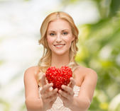 Smiling woman giving small red heart — Stock Photo