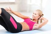 Donna sportiva facendo esercizio sul pavimento — Foto Stock