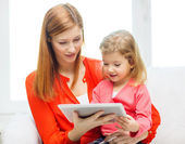 Happy mother and daughter with tablet pc computer — Stok fotoğraf