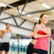 Stock Photo: Group of smiling people stretching in the gym