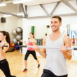 Stock Photo: Group of smiling people working out with barbells