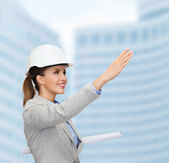 Smiling architect in white helmet with blueprints — Stock Photo