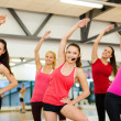 Stock Photo: Group of smiling people stretching in gym